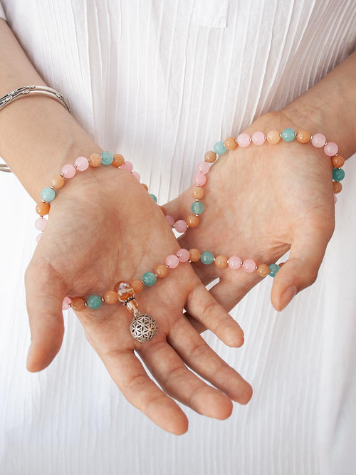 Burgeoning Flower Mala in complementary hues of aventurine has a crystal Guru and 925 silver flower of life. Hand view.