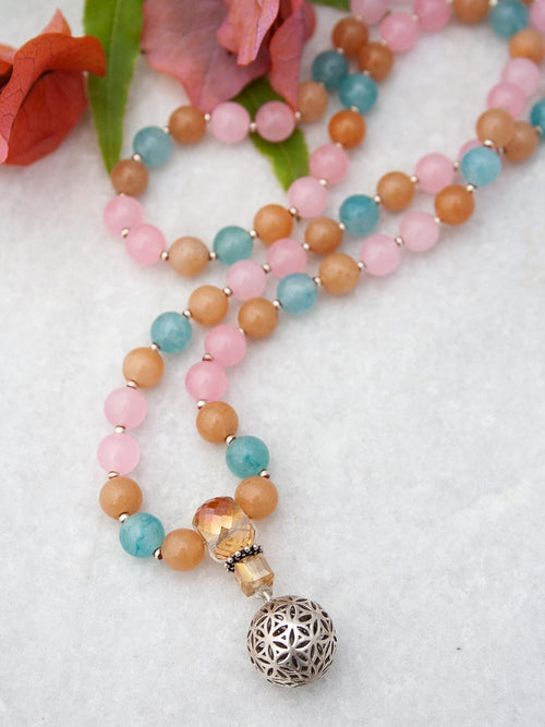 Burgeoning Flower Mala in complementary hues of aventurine has a crystal Guru and 925 silver flower of life. Full view.