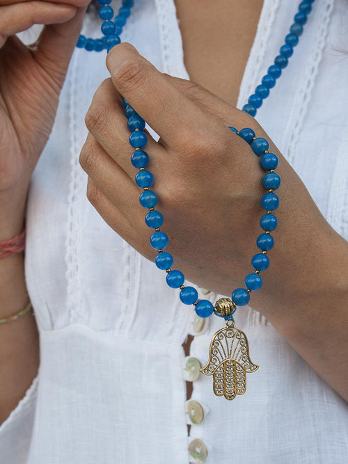 Success Mala, in 8mm absolute blue onyx, has brass Guru and Hamsa Hand. Hand view