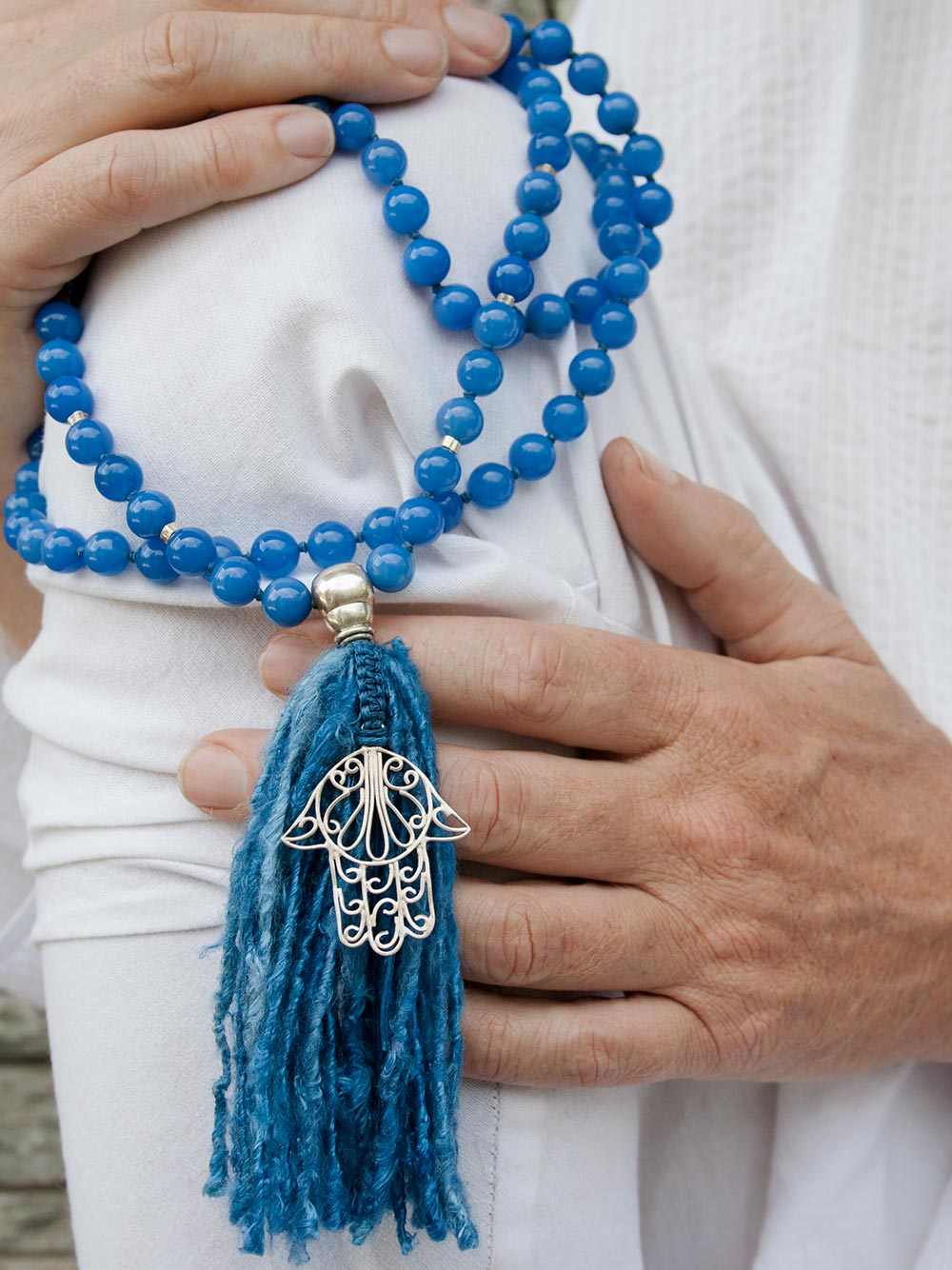 Strength Mala, in absolute blue 10mm onyx, has a 925 silver Guru and Hamsa Hand, and sari silk tassel. Hand view