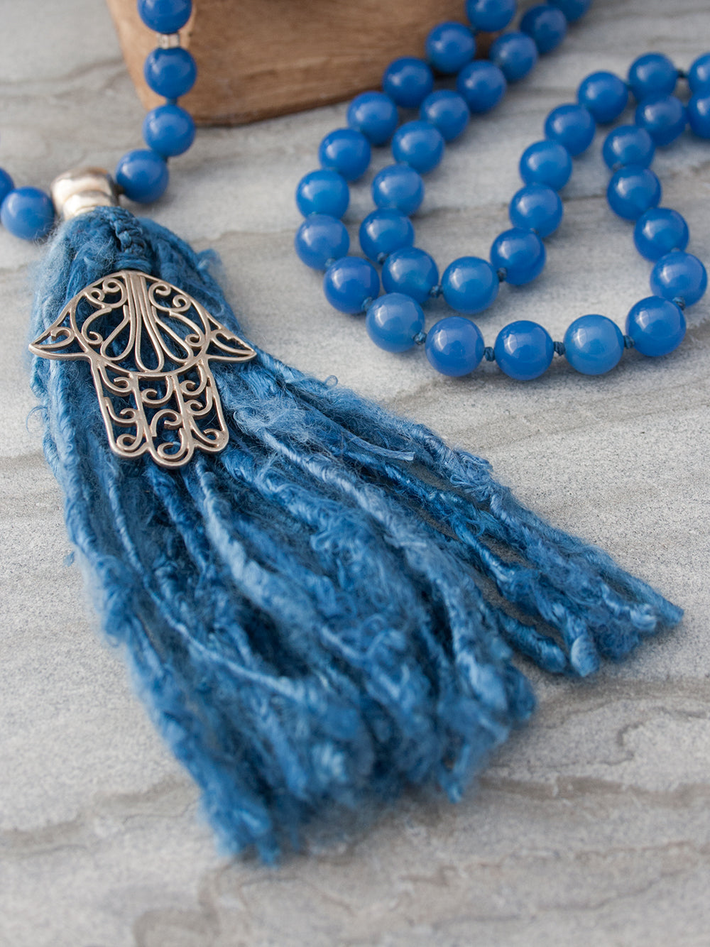 Strength Mala, in absolute blue 10mm onyx, has a 925 silver Guru and Hamsa Hand, and sari silk tassel. Hamsa Hand tassel view