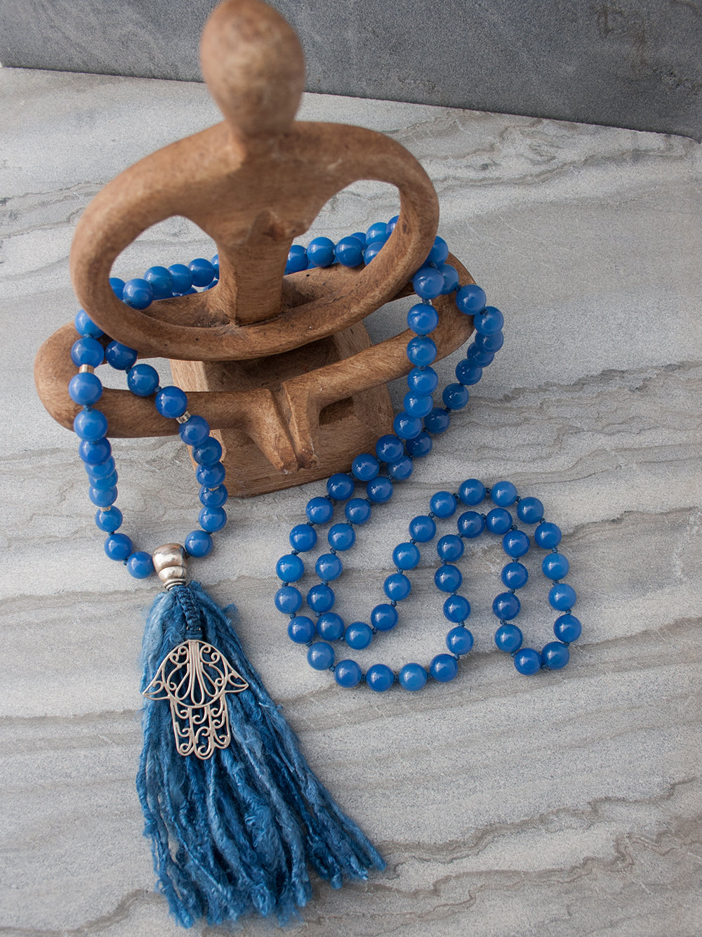Strength Mala, in absolute blue 10mm onyx, has a 925 silver Guru and Hamsa Hand, and sari silk tassel. Full view