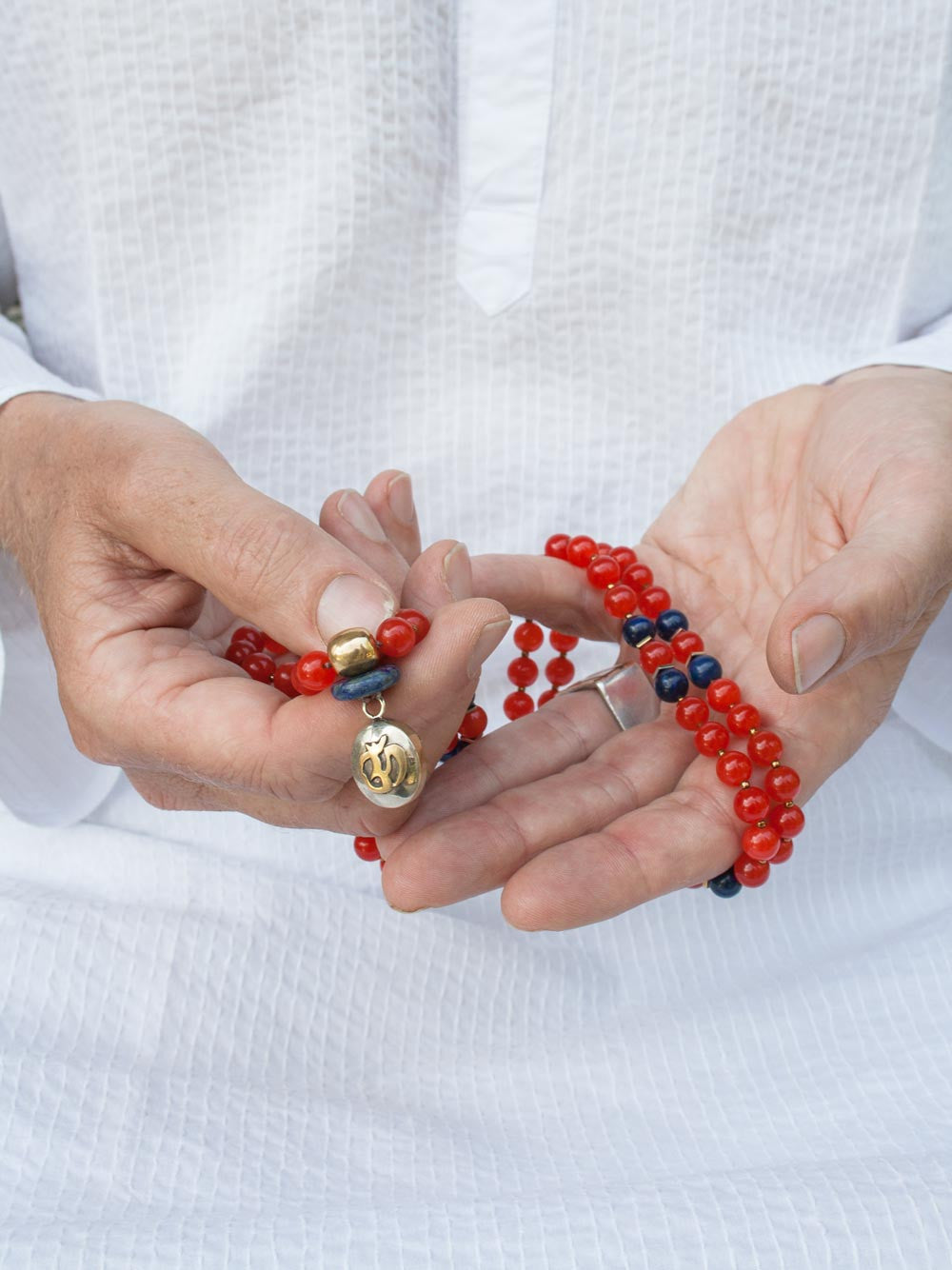 The Whispering Om Mala is made in Mandarin orange aventurine ~ the whisper stone ~ and lapis lazuli, with brass Guru bead and Om pendant: hand view.
