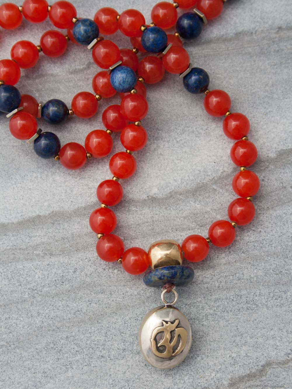 The Whispering Om Mala is made in Mandarin orange aventurine ~ the whisper stone ~ and lapis lazuli, with brass Guru bead and Om pendant: Guru bead and Om view.