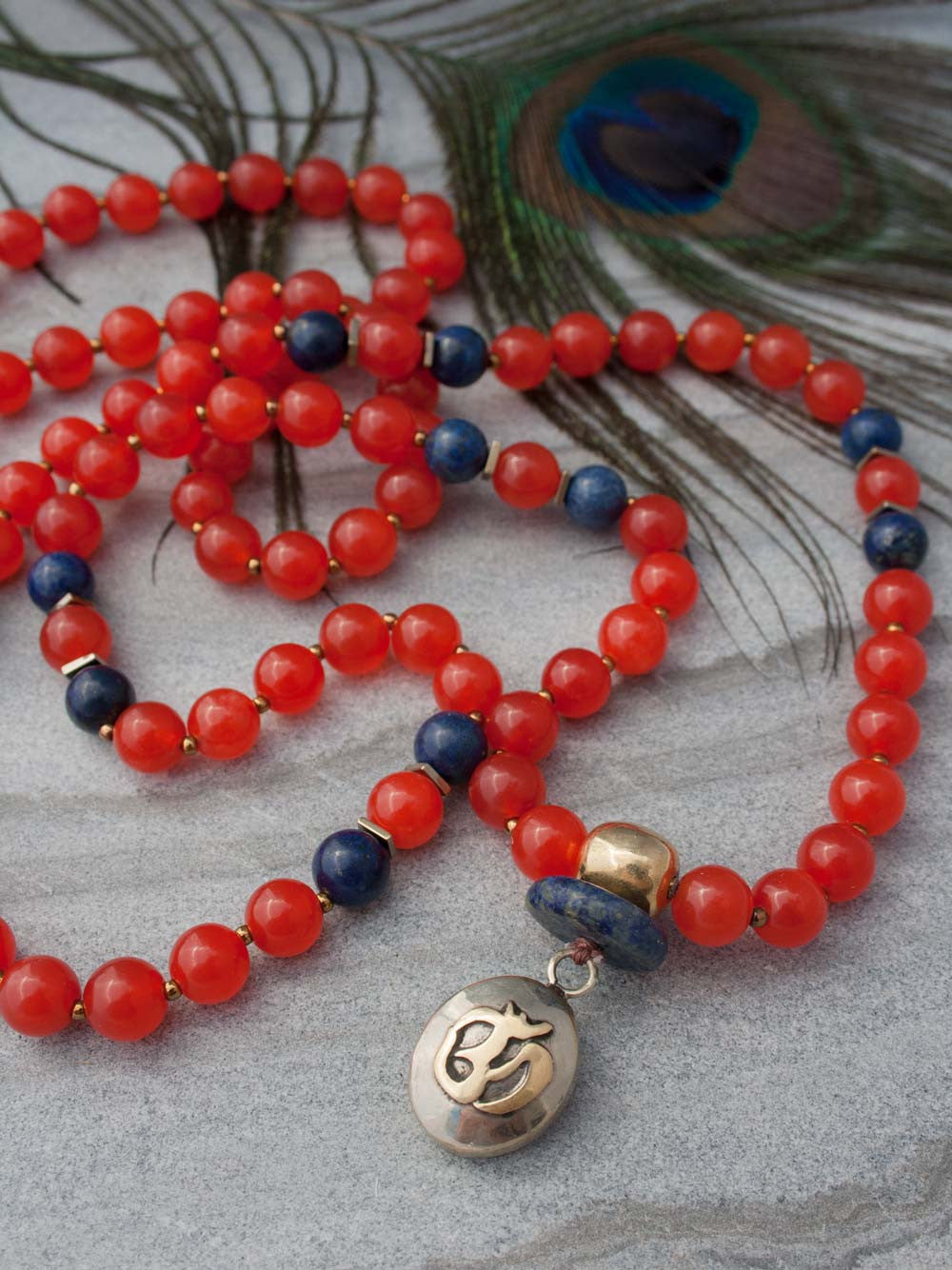 The Whispering Om Mala is made in Mandarin orange aventurine ~ the whisper stone ~ and lapis lazuli, with brass Guru bead and Om pendant: partial view.