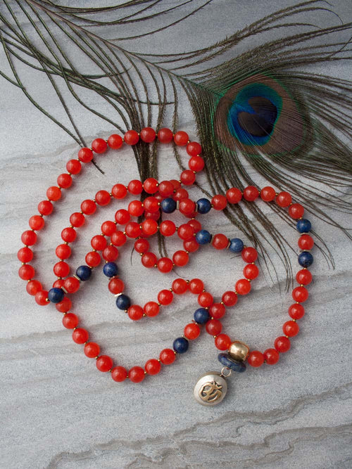 The Whispering Om Mala is made in Mandarin orange aventurine ~ the whisper stone ~ and lapis lazuli, with brass Guru bead and Om pendant: full view.