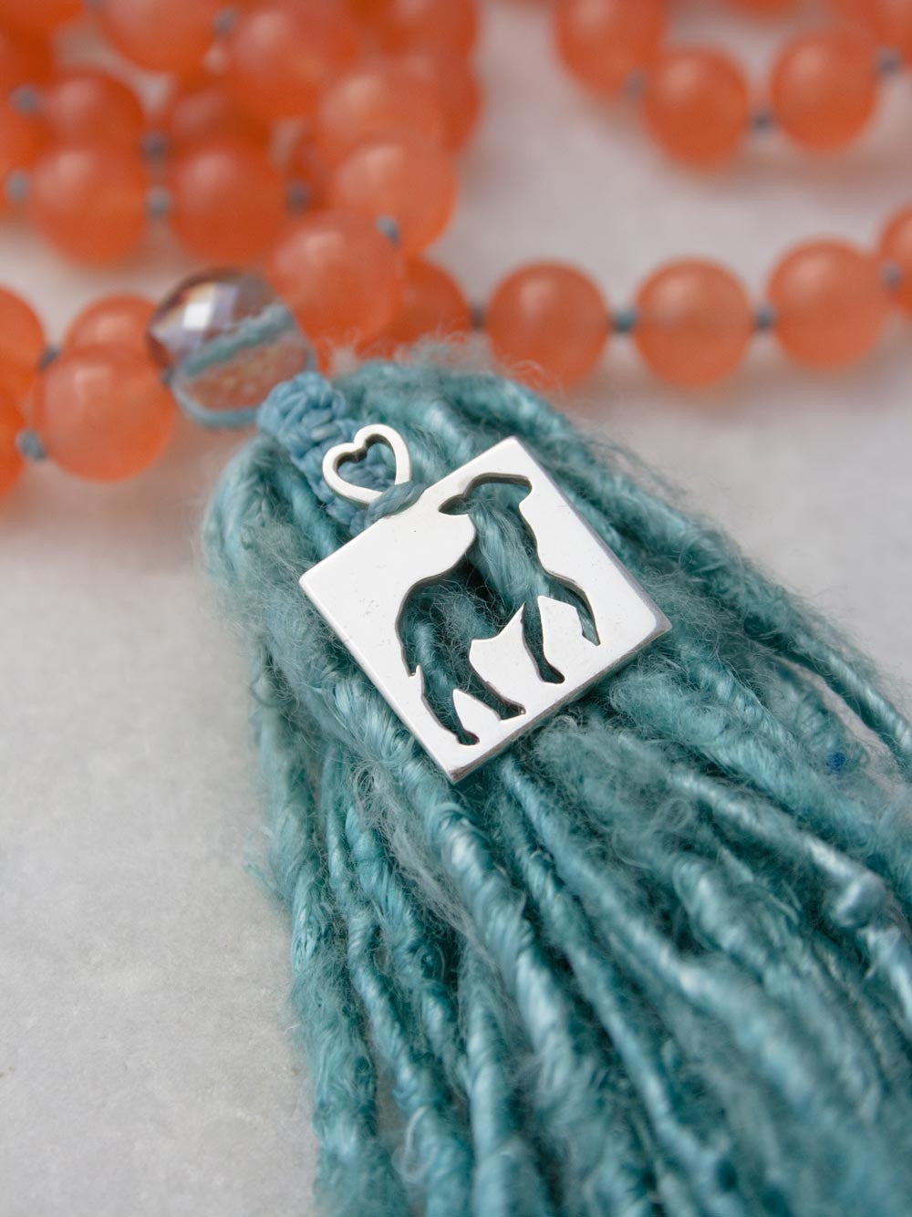 Our sweet and spunky Tribe of Lambs Mala in 10mm Tuscan peach aventurine with silver Tribe of Lambs pendant and sari silk tassel: pendant view.