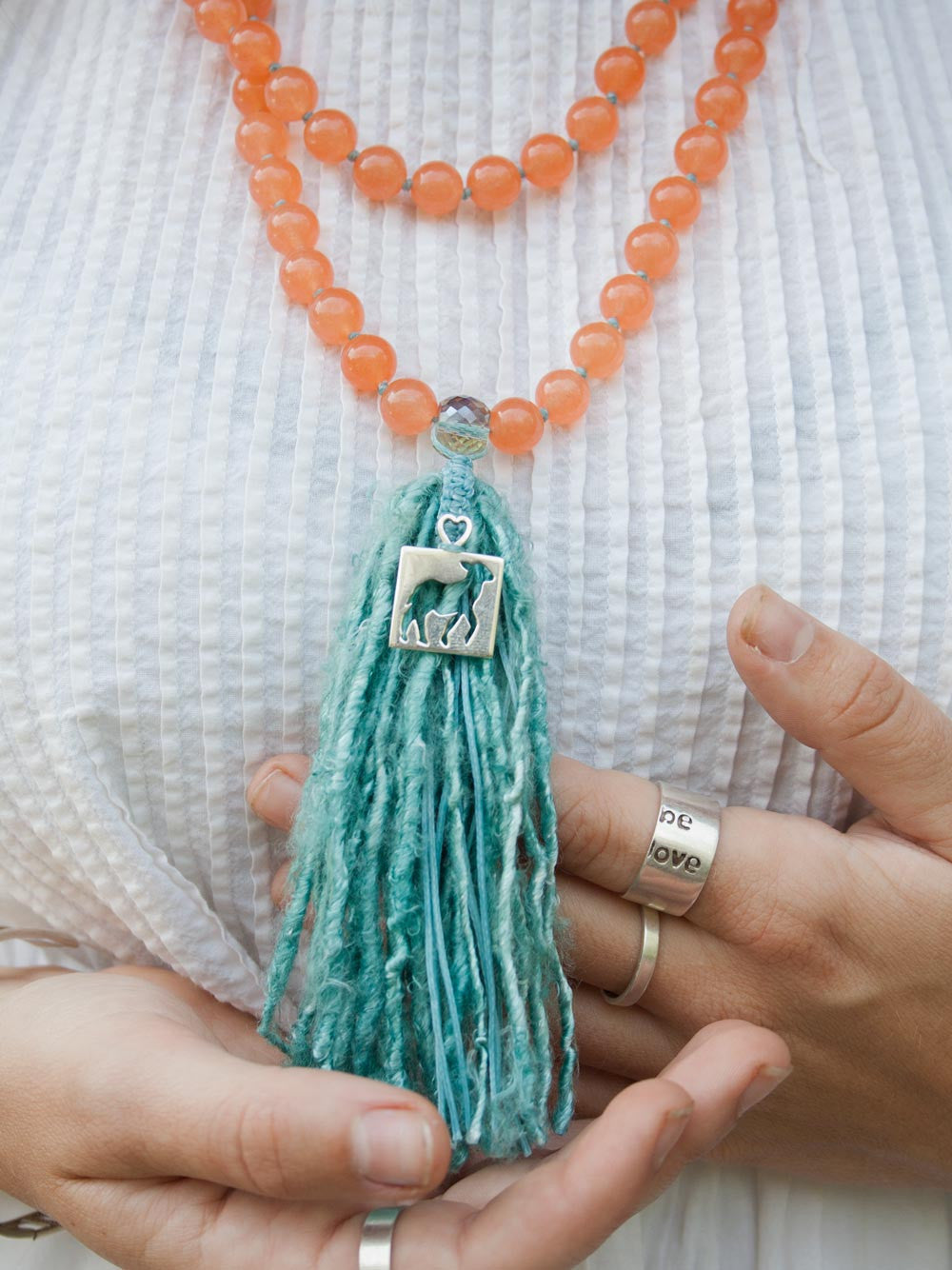 Our sweet and spunky Tribe of Lambs Mala, in 10mm Tuscan peach aventurine with silver Tribe of Lambs pendant and sari silk tassel: hand view.
