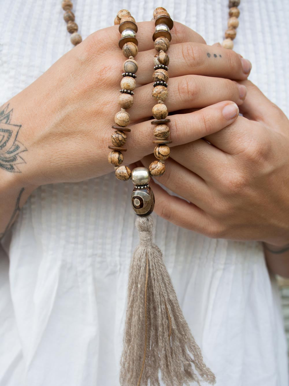 Our Shelter Mala is hand-knotted in fascinating picture jasper, with 925 silver accents, Tibetan agate amulet, and pashmina tassel: hand view.