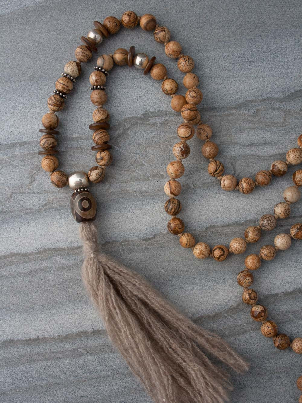 Our Shelter Mala is hand-knotted in fascinating picture jasper, with 925 silver accents, Tibetan agate amulet, and pashmina tassel: partial view.