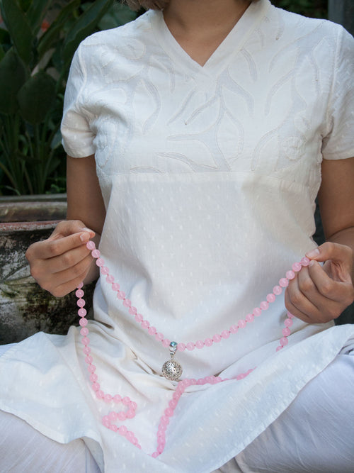 Blossoming Flower Mala in rose pink aventurine has crystal Guru and 925 silver flower of life. Hand view.