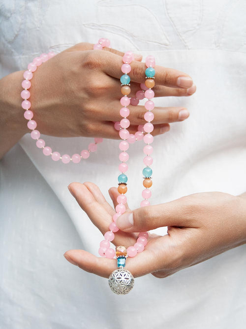 Budding Flower Mala in 8mm rose pink aventurine has complementary accents and crystal guru and 925 silver flower of life. Hand view.