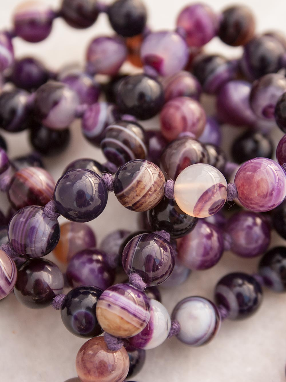The Aquarius Mala in a violet twirl of Onyx & Agate, features a Guru setting in Tibetan Silver, Chinese Marble and Amethyst. Bead view.