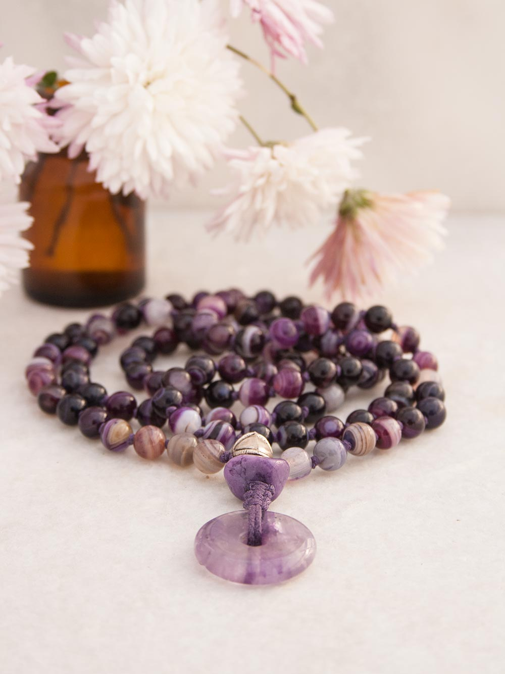 The Aquarius Mala in a violet twirl of Onyx & Agate, features a Guru setting in Tibetan Silver, Chinese Marble and Amethyst. Full view alternate.