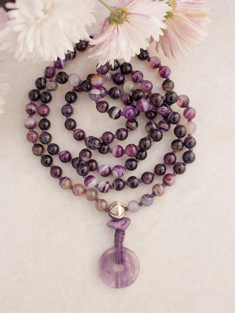 The Aquarius Mala in a violet twirl of Onyx & Agate, features a Guru setting in Tibetan Silver, Chinese Marble and Amethyst. Full view.