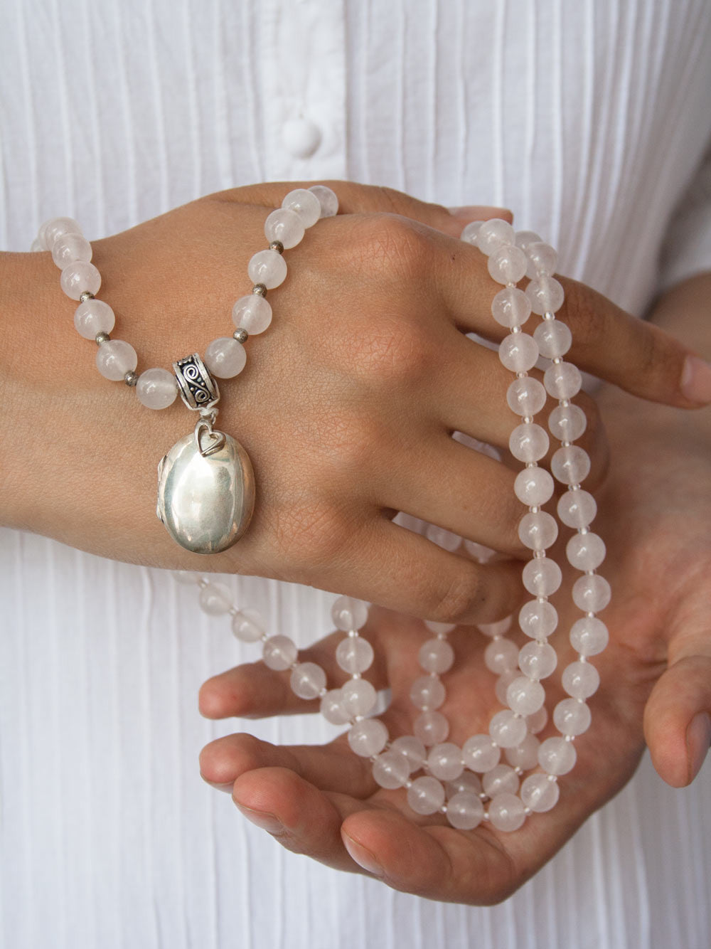 Eternal Love Mala, made with heart in rose quartz, has a silver etched Guru bead, & oval locket & heart: hand view
