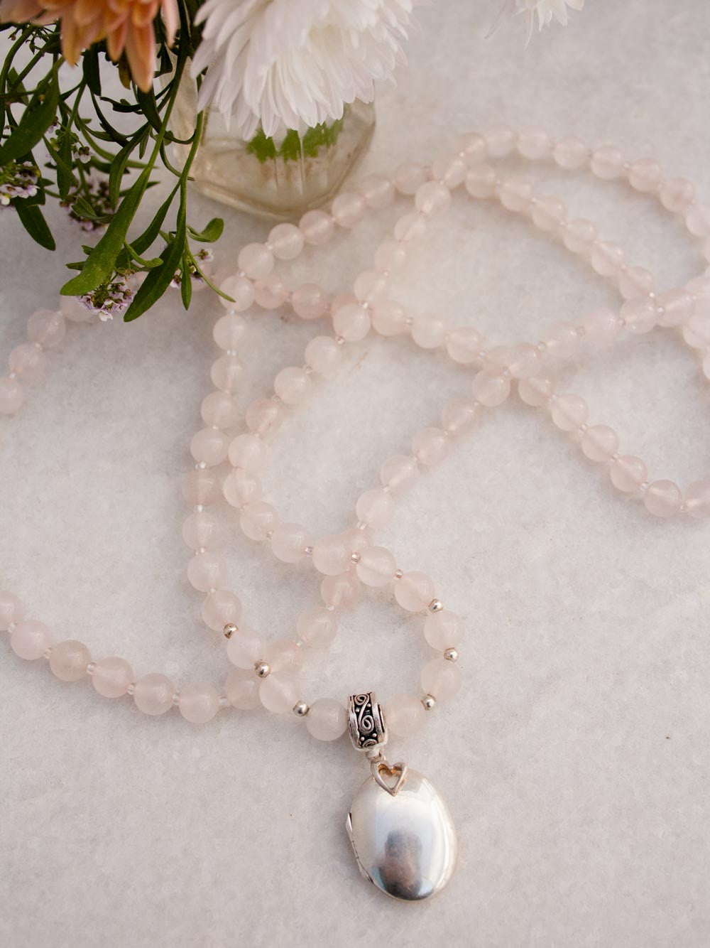 Eternal Love Mala, made with heart in rose quartz, has a silver etched Guru bead, & oval locket & heart: full view