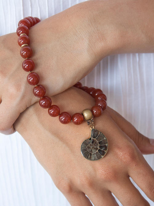 To Infinity... a 27 bead hand-held Mala in spectacular sienna 10mm onyx,  with brass Guru bead and ammonite nautilus: hand view.
