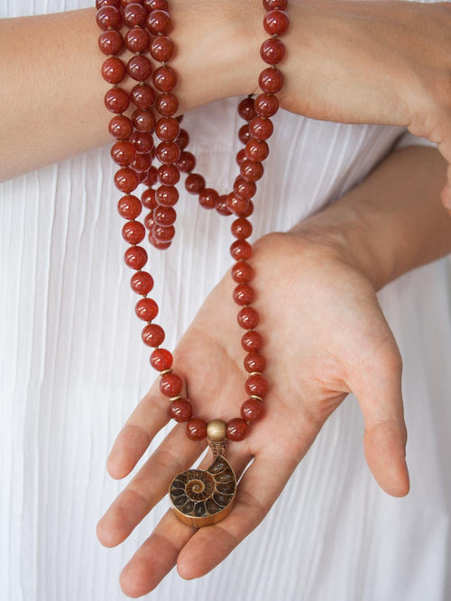 To Infinity... a 108 bead Mala in spectacular sienna onyx, 10mm, with brass Guru bead and ammonite nautilus pendant: hand view.