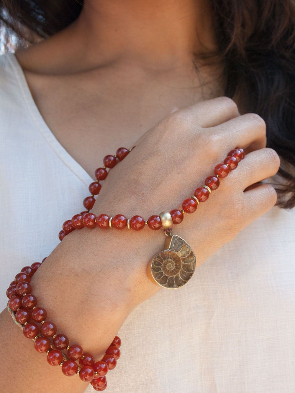 To Infinity... a Mala for celebration, in 8mm sienna Onyx with brass Guru bead and ammonite Nautilus pendant: hand view.