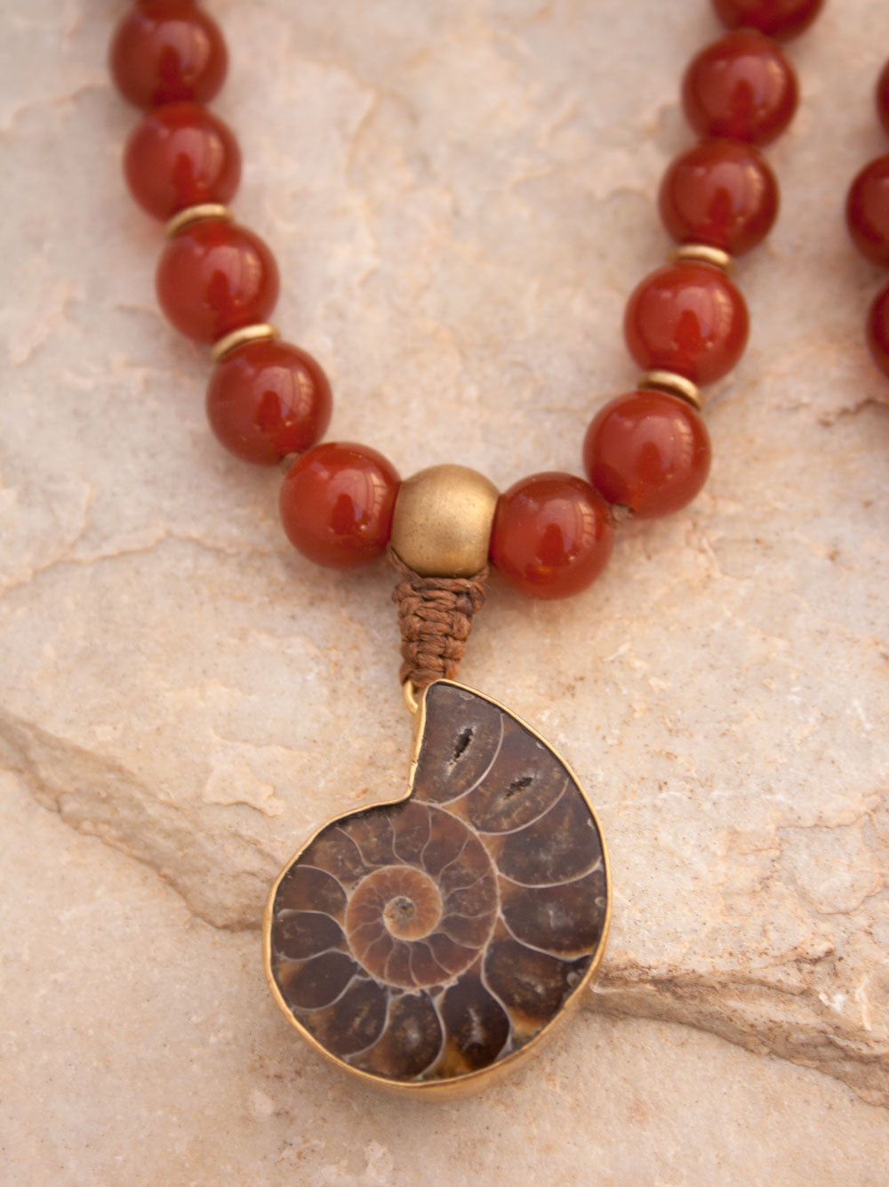 To Infinity... a 108 bead Mala in spectacular sienna onyx, 10mm, with brass Guru bead and ammonite nautilus pendant: view of nautilus.