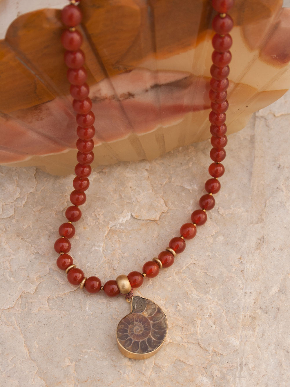 To Infinity... a Mala for celebration, in 8mm sienna Onyx with brass Guru bead and ammonite Nautilus pendant: partial view.