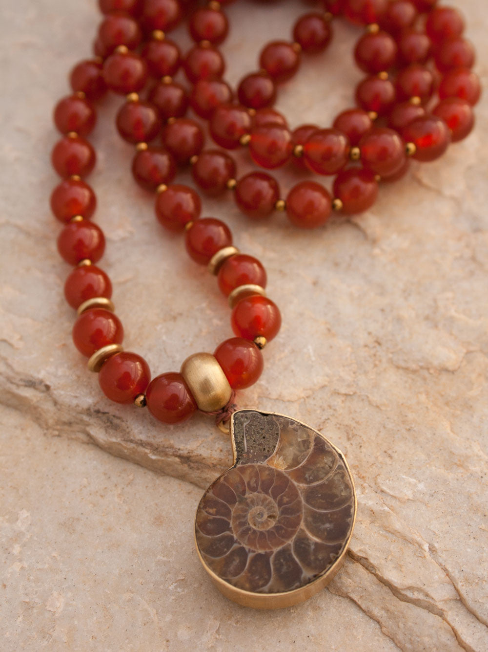 To Infinity... a Mala for celebration, in 8mm sienna Onyx with brass Guru bead and ammonite Nautilus pendant: Guru bead and Nautilus view.