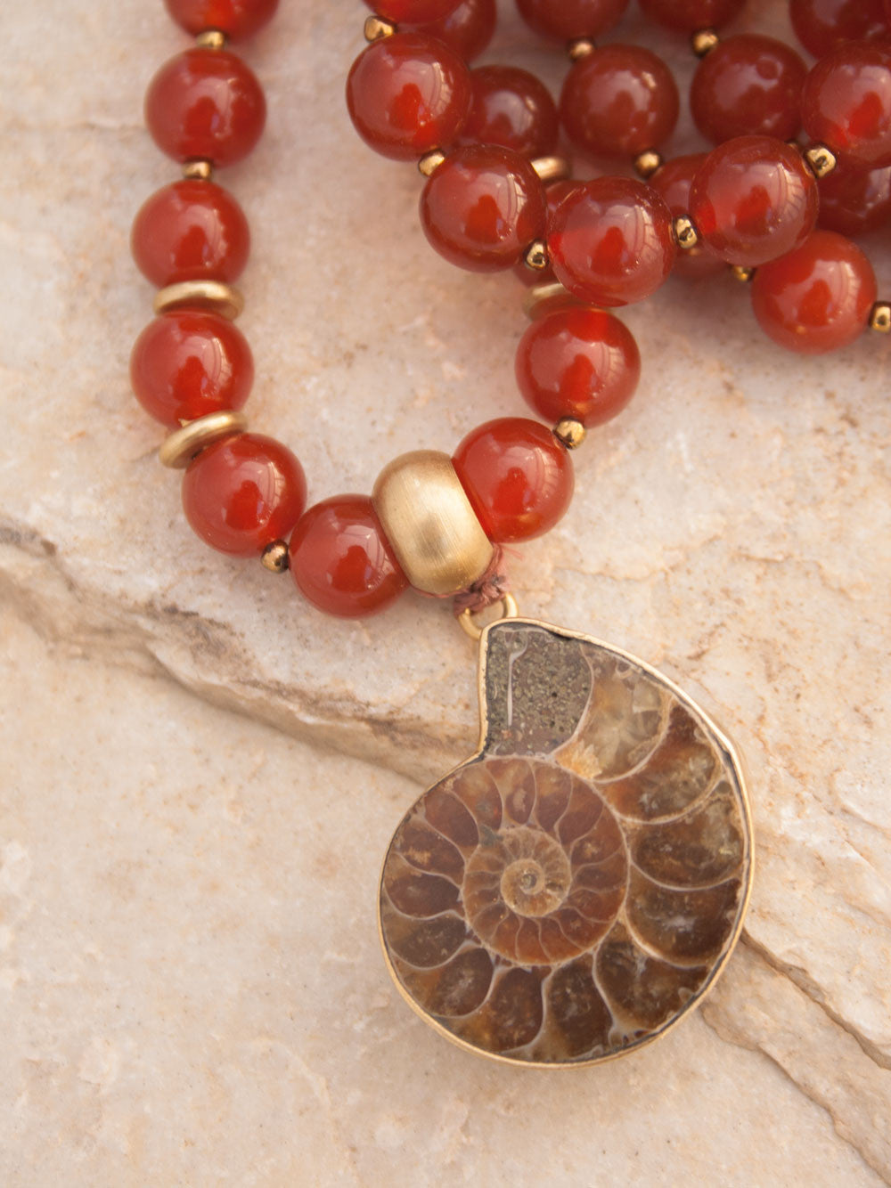 To Infinity... a Mala for celebration, in 8mm sienna Onyx with brass Guru bead and ammonite Nautilus pendant: Guru bead and Nautilus closeup view.