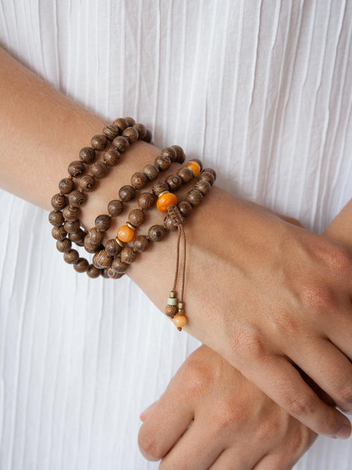 Eternal Existence Wrist-wrap Mala is hand-knotted with heart in 8mm Wengewood, with amber accents, a macrame slide, & beaded tassel: hand view