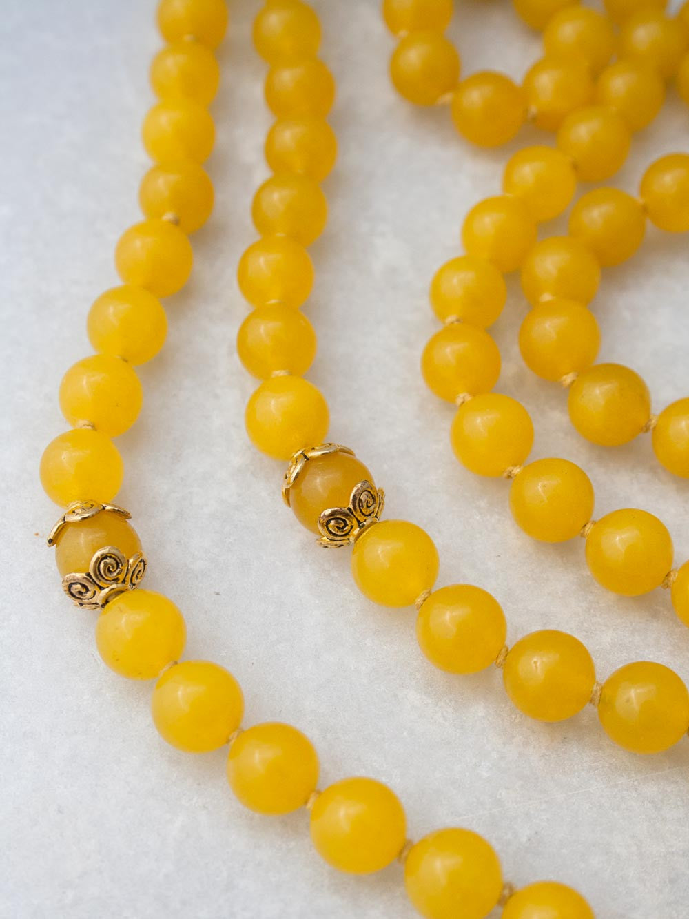 Our Splendour Mala, in aurora gloria yellow aventurine, has a brass Guru bead & glorious Shri Yantra pendant: view beads and spacers