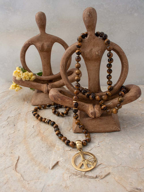 Imagine Mala, in tiger's eye, has a peace/dove symbol handcrafted in brass: full view