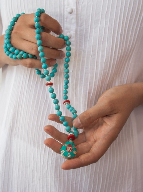 Om Mani Padme Hum Mala in capriccio blue howlite has coral accents and 925 silver/coral/turquoise pendant: hand view