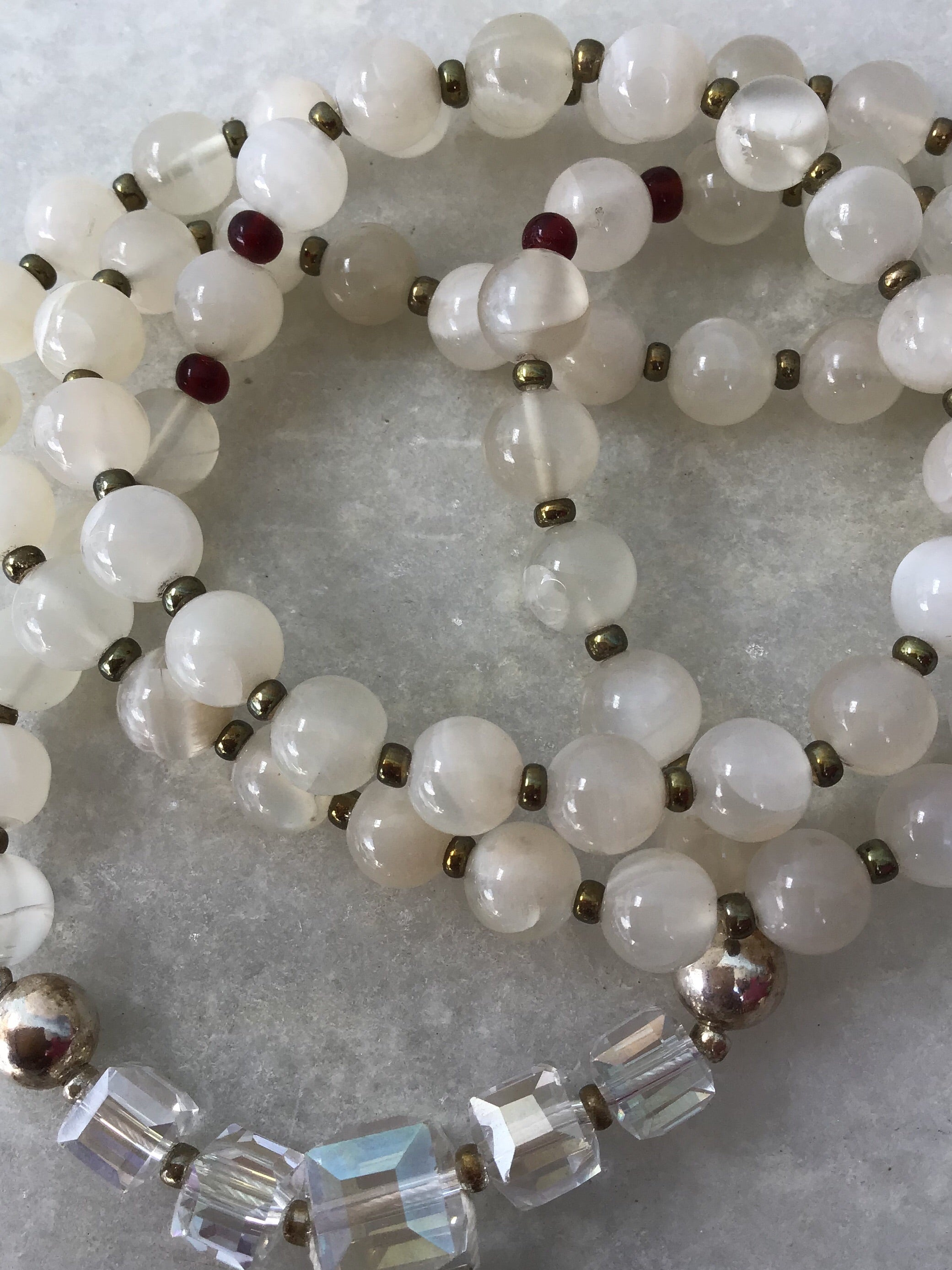 Moon Goddess Mala in celestial moonstone with garnet and 925 silver accents and stellar drusy agate Guru setting. Closeup bead view.