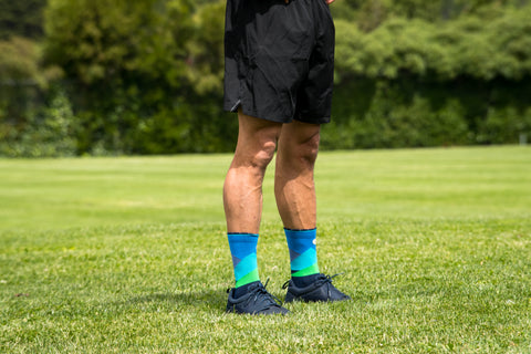 Man standing in a field wearing Lily Trotters Over the Moon - Blue crew-length compression socks