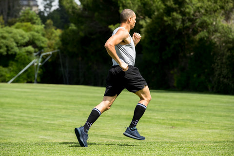 Man running in full-length Lily Trotters compression socks in a field