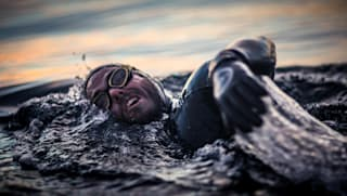 Close up of a man swimming in the ocean in a wetsuit