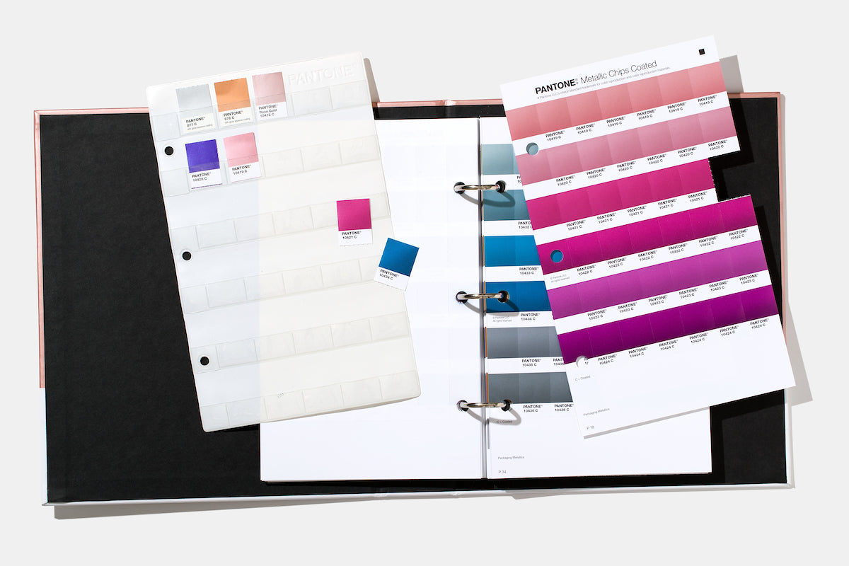 Pantone Metallics Chips Book opened in a 3 ring binder with ripped out paper chips and pages