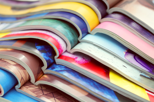 Several magazines opened and on top of each other as an example of coated paper