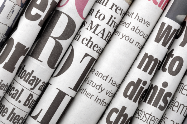 Several newspapers opened and on top of each other as an example of uncoated paper