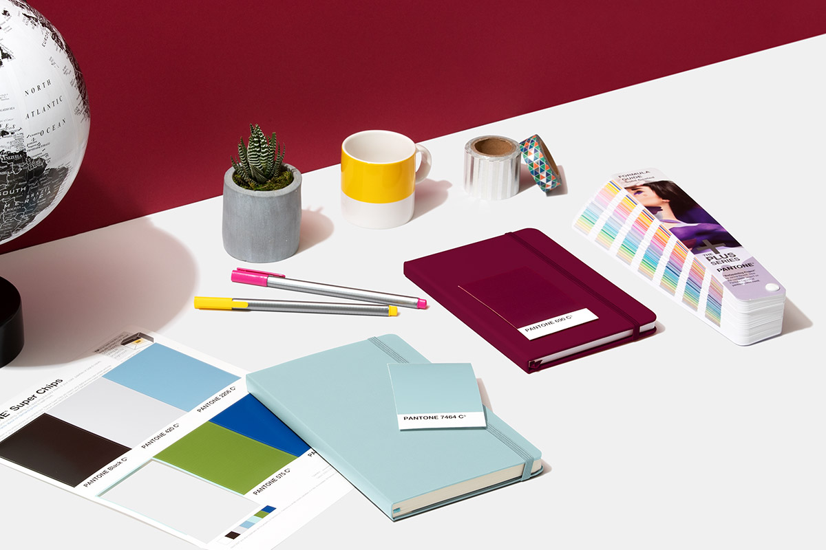 Pantone Super Chips with notebooks and the formula guide on a desk