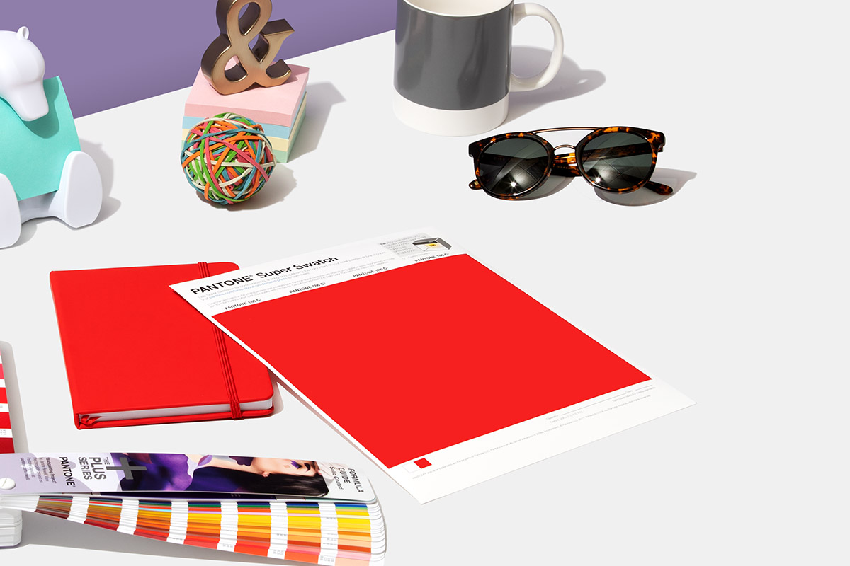 Red Super Swatch on a table with a formula guide, notebook, sun glasses, and mug
