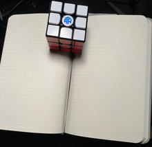 Lined notebook with speed cube separating pages and showing the built-in bookmark.