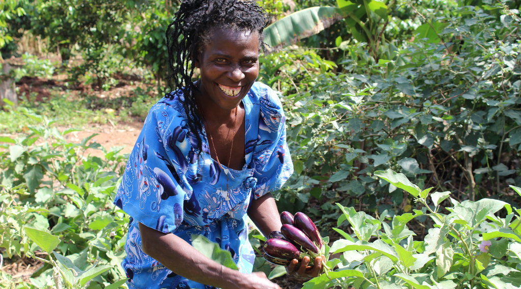 Agriculture Project in Uganda. Woman holding vegetables.