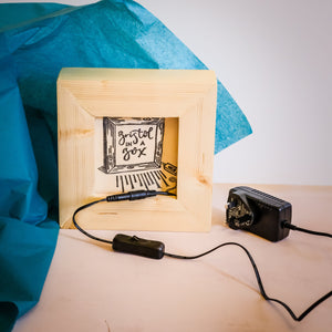 Wooden light box with its plug and on/off switch on