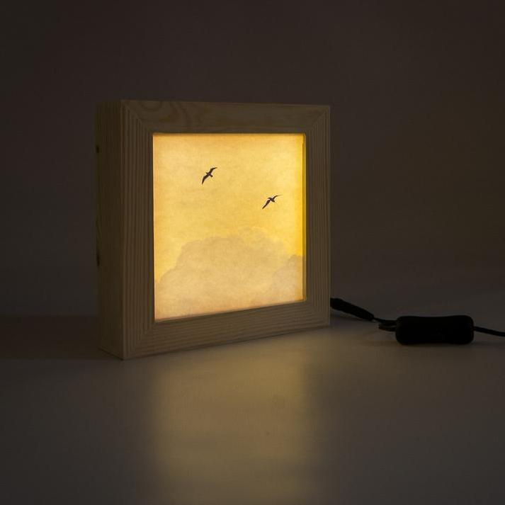 A seagull print in its wooden light box glowing in low light