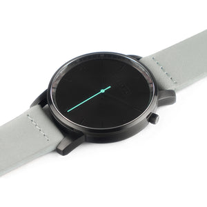 All black Hervor watch with dove grey leather strap and a turquoise accent second hand