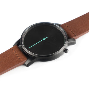 All black Hervor watch with fox brown leather strap and a turquoise accent second hand