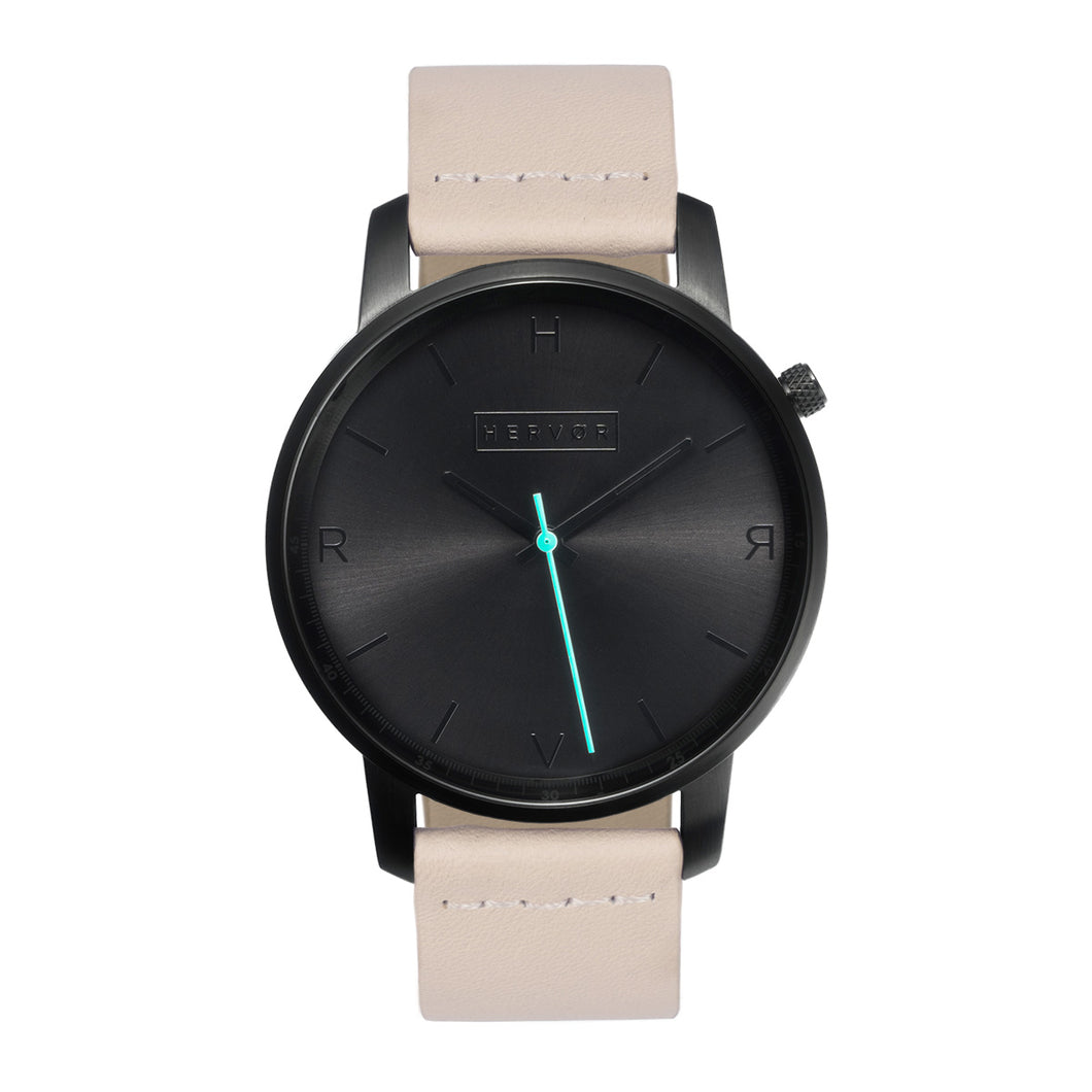 All black Hervor watch with light pink skin tone leather strap and a turquoise accent second hand