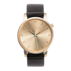 All gold Hervor watch with black leather strap and a turquoise accent second hand