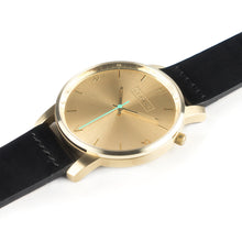 Load image into Gallery viewer, All gold Hervor watch with black leather strap and a turquoise accent second hand